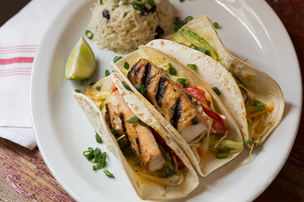 Image of Baja Fish Tacos - Grilled Mahi-Mahi, Corn Tortillas, Avocado, Coleslaw, Jalapeño Aioli. Black Bean & Coconut Rice, Corn Salsa