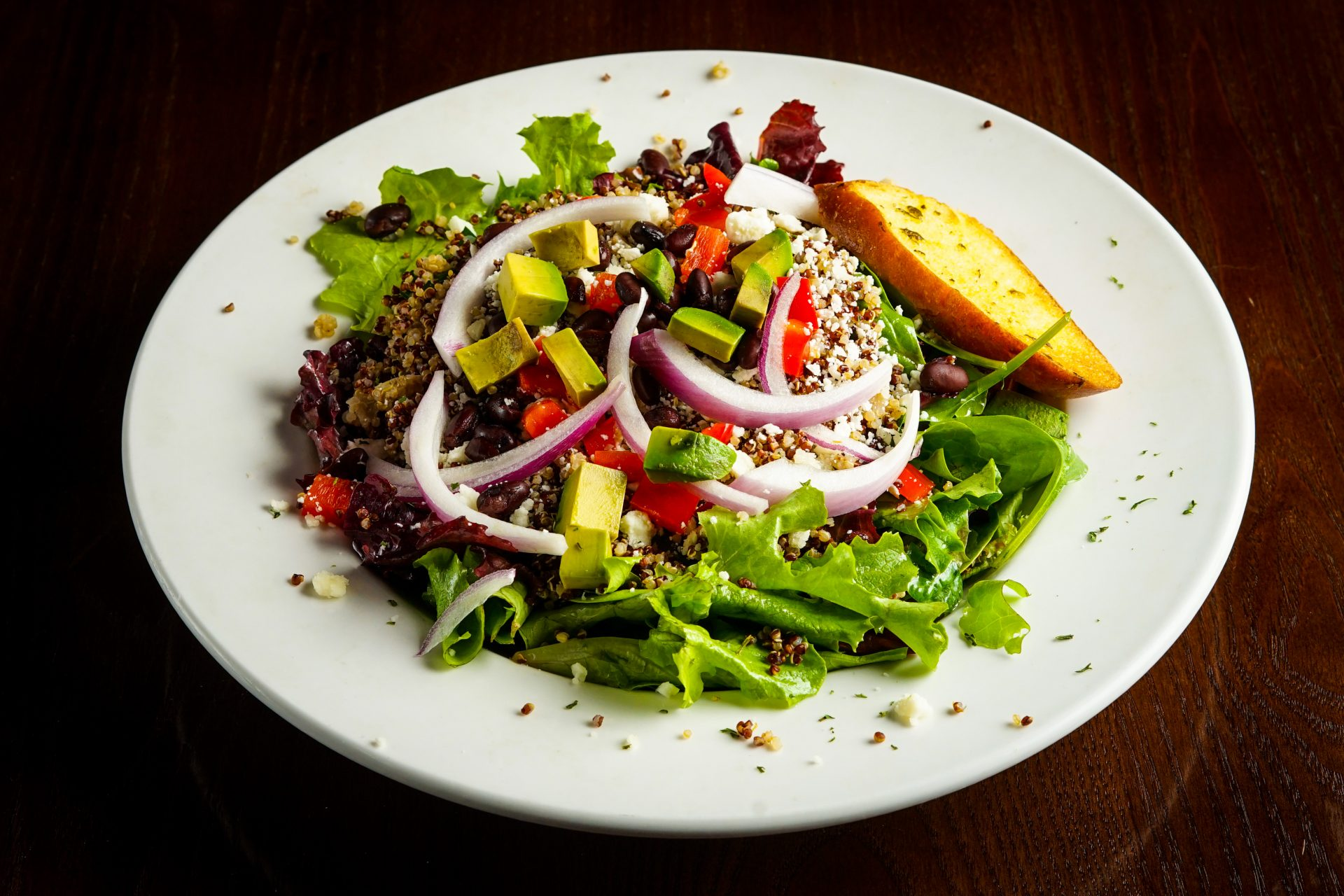 Image of Quinoa Salad  - Red & White Quinoa, Mixed Greens, Avocado, Red Onion, Black Bean, House Vinaigrette, Red Pepper, Queso Fresco, Crostini